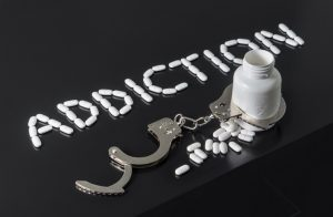 """The word """"Addiction"""" spelled with pills with a bottle and handcuffs beneath it."""