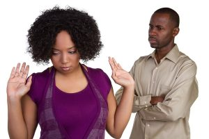 A man and woman that seem to be in an argument. She has her hands up in a defensive, closed-off posture and his arms are crossed in front of him, visibly frustrated.