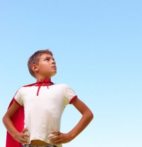 A young boy wearing a red superhero cape
