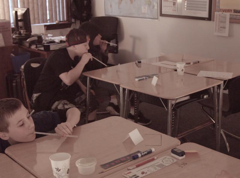 children blowing paper through a straw across their desk