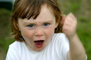 A young girl looking angry, shaking her fist in the air