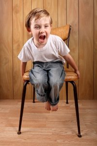A young boy, sitting on a chair, yelling.