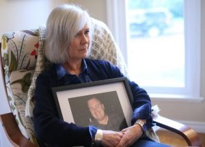 Jennifer Howard lights a candle surrounded by photos of son Robert Cunningham, who died of a fentanyl overdose.