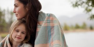 A mom and her daughter snuggled together under a blanket