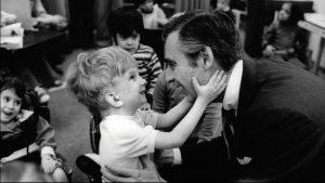 a small boy, hugging Mr. Rogers