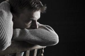 man depressed resting head on chair