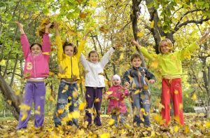 kids jumping in leaves