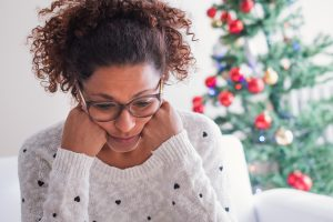 Worried black young woman sitting in the living room at home during christmas holiday