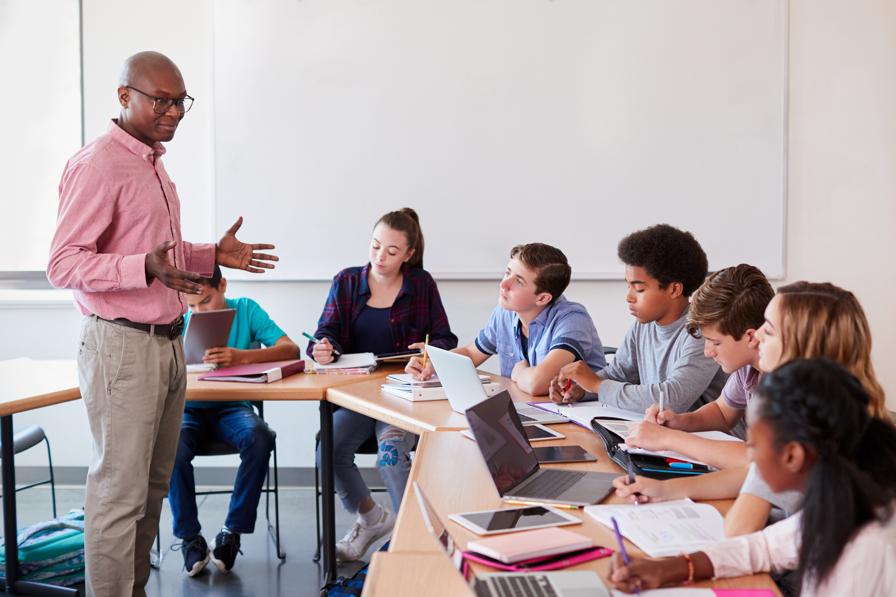 Male African American teacher teaching students