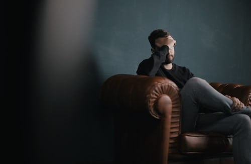 man on couch with hand over his face