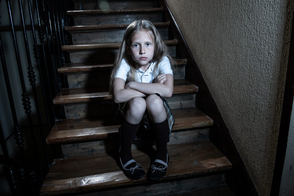 Sad, depressed, unhappy schoolgirl suffering from abuse feeling lonely and hopeless sitting on stairs with dark light.
