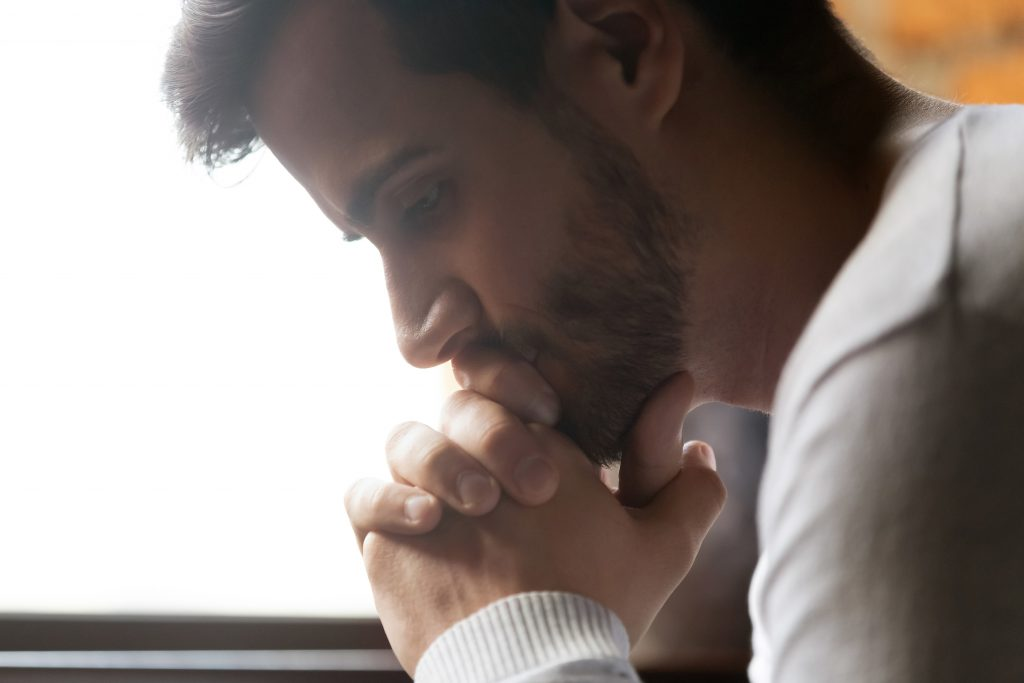 Close up of pensive male thinking of personal problems
