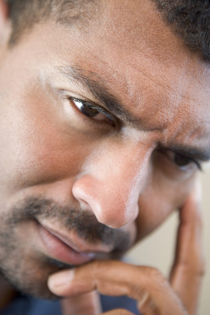 Head shot of worried man with his hand to his face
