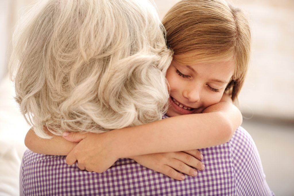 I love you. Affectionate granddaughter and grandmother are hugging. Girl is smiling with closed eyes