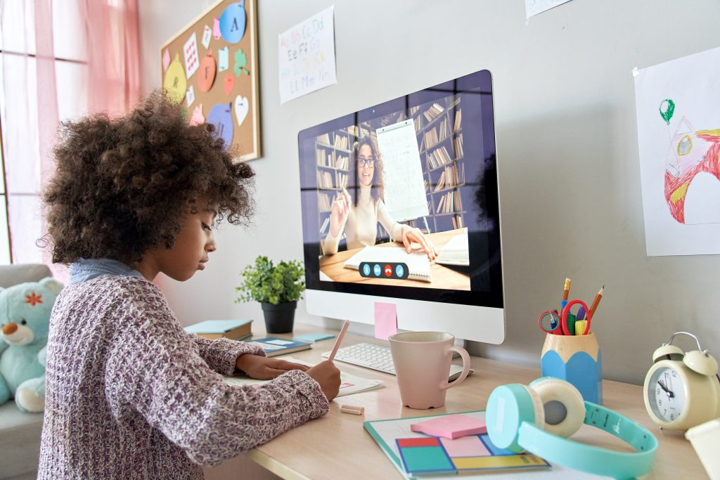African primary school kid girl distance learning by video conference call chat with remote teacher. Virtual education.