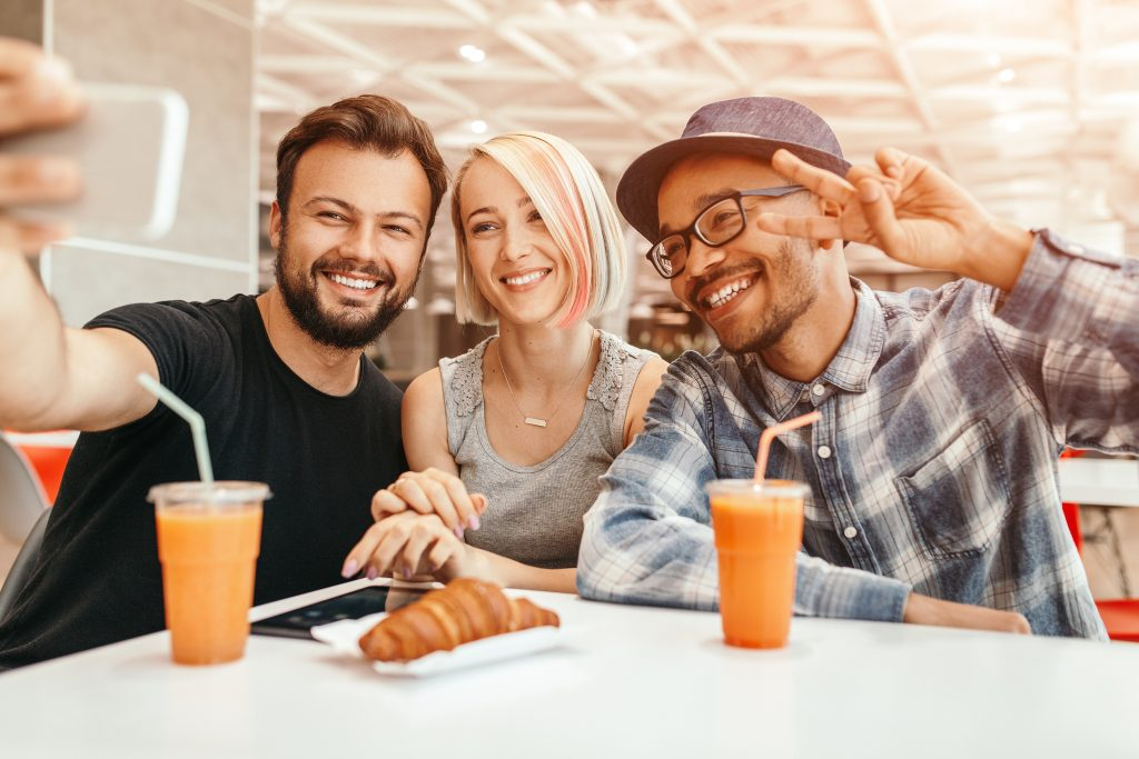 Delighted multiracial men and woman smiling and taking selfie while having lunch in cafe together