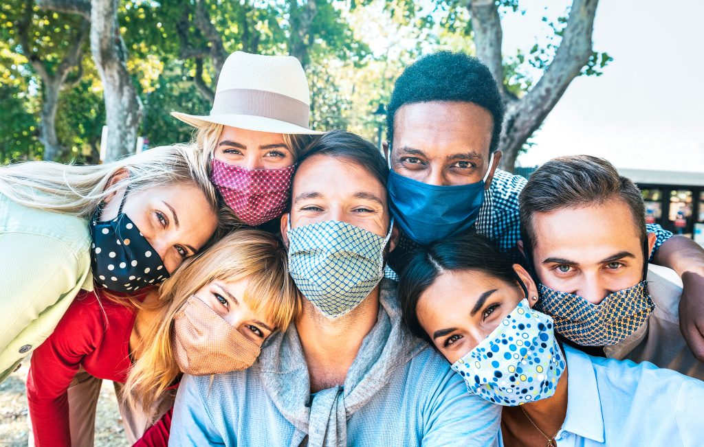 Multiracial friends taking selfie with closed face masks during Covid second wave outbreak - New normal concept.