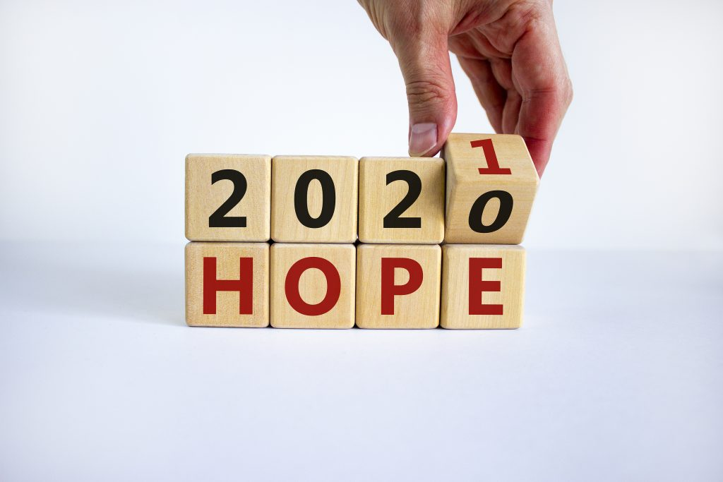 Male hand flips a wooden cube and changes the inscription Hopes 2020 to Hopes 2021
