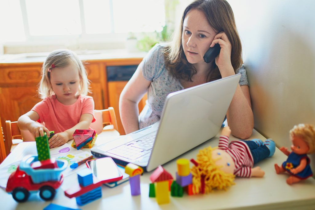Exhausted and stressed mother working from home with toddler. Child making noise and disturbing woman trying to work.