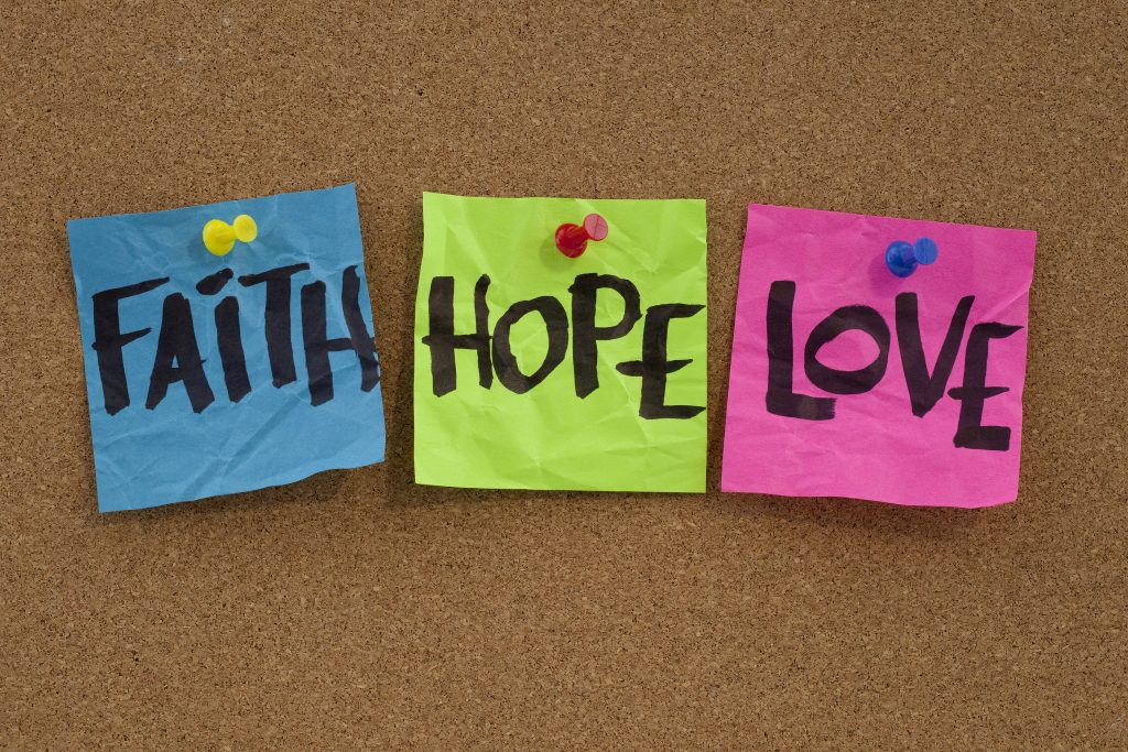 spiritual reminder - faith hope and love handwritten on colorful notes and posted on cork bulletin board