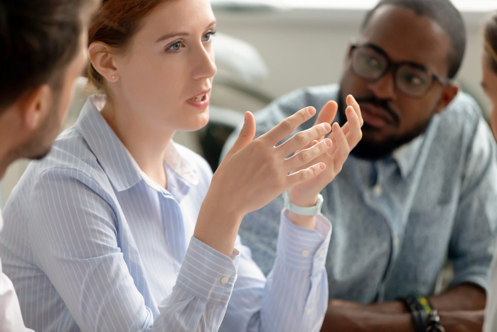 Focused female business woman talking at diverse group meeting