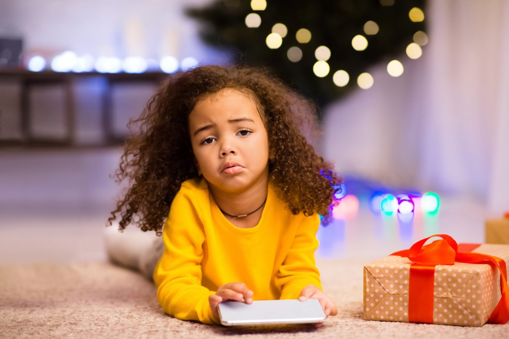 stressed african american girl near Christmas tree