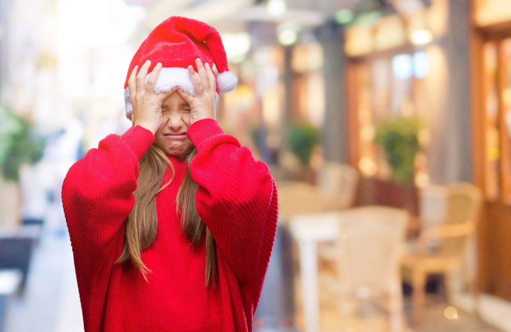 Young wearing christmas hat stressed with Hands on head.