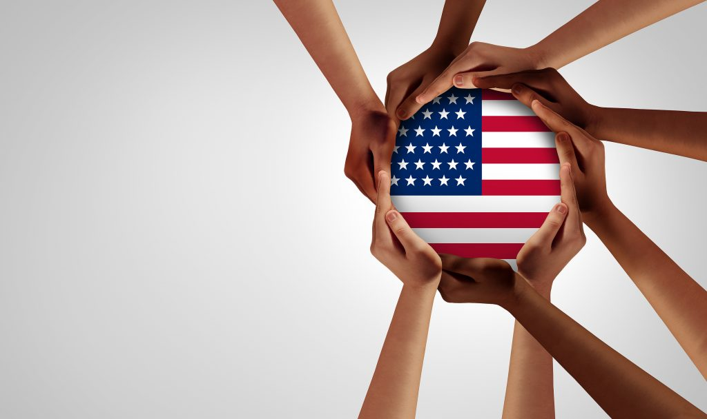 American Unity and diversity partnership as hands in a group of diverse people connected together shaped as a support community symbol of a group