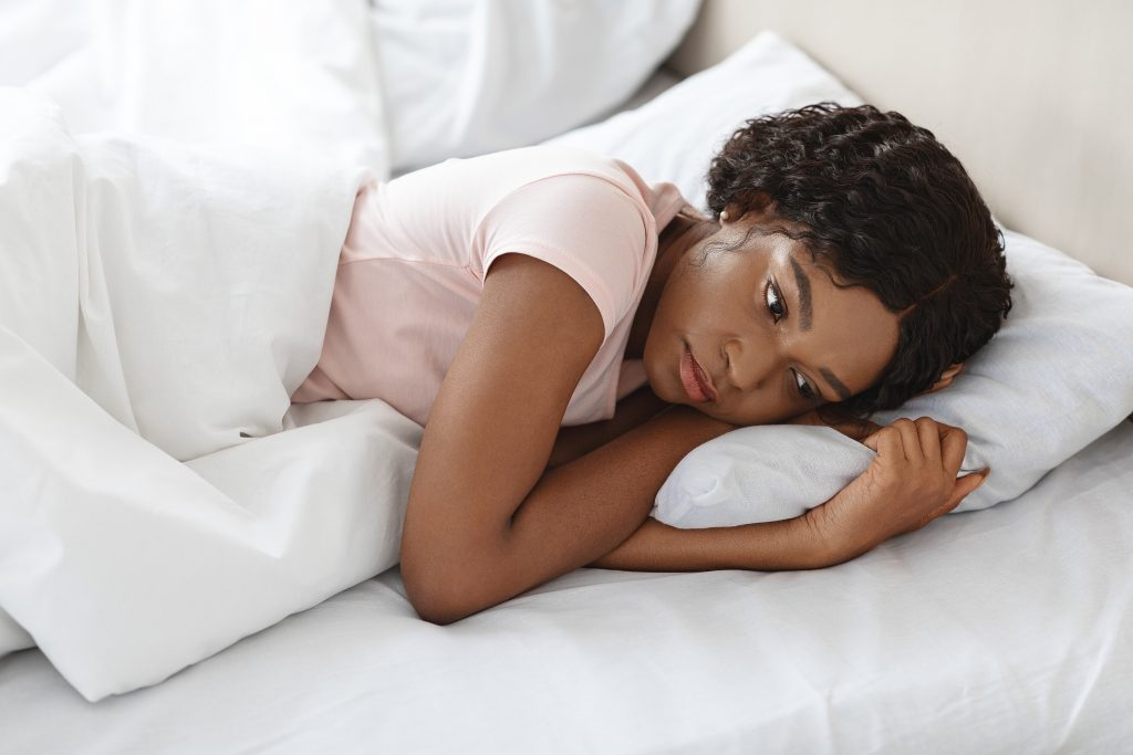 Sad african american lady feeling lonely, spending day in bed