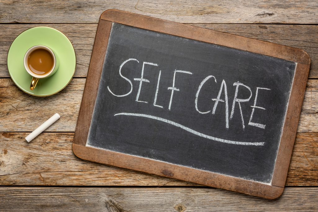Self care - white chalk handwriting on a blackboard with a cup of coffee