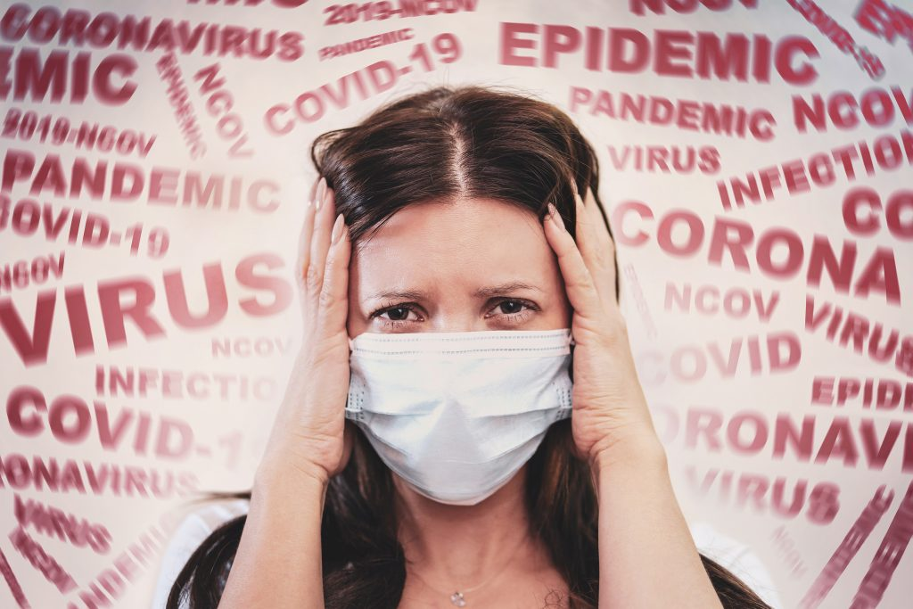 a woman with a mask on her face, scared and fearful about the coronavirus/covid.