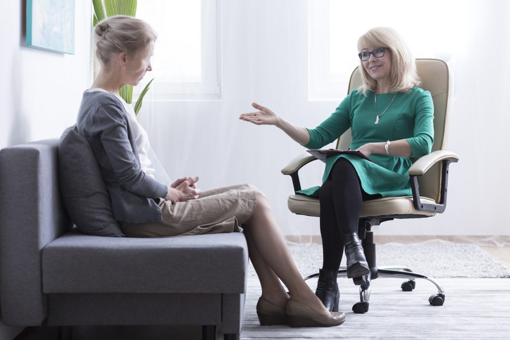 counseling from friendly female psychiatrist, sitting in bright office on sofa