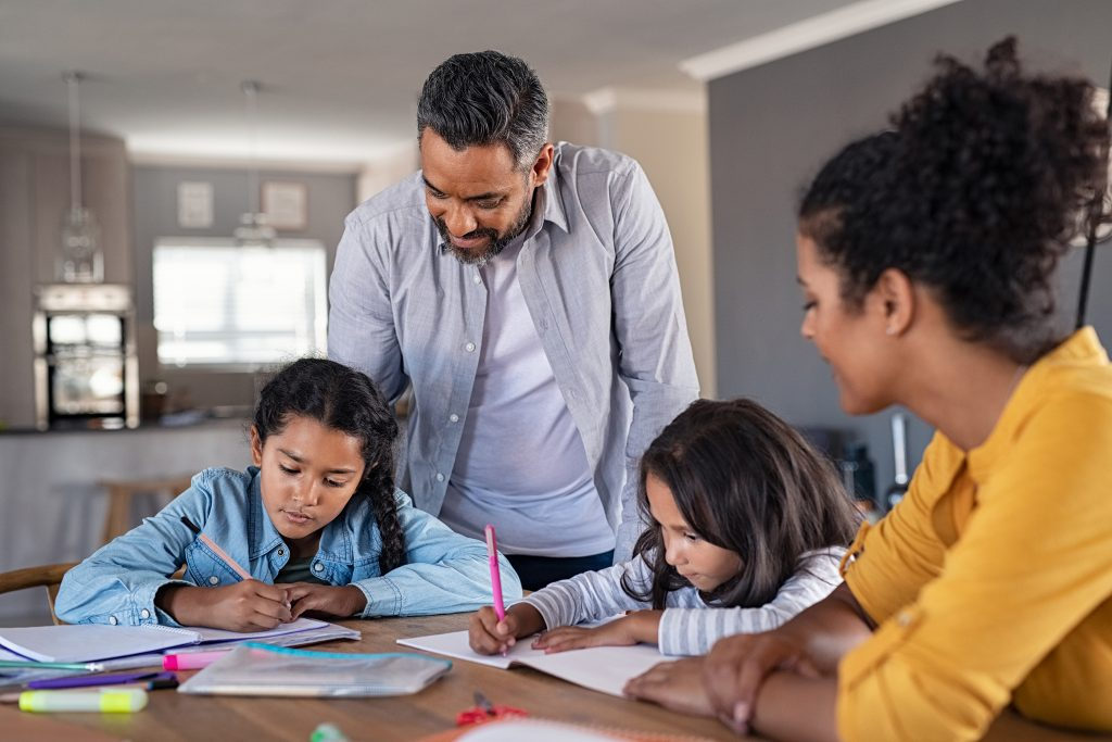Middle eastern father and african mother helping daughters studying at home.