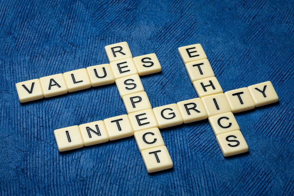 integrity, respect, values and ethics crossword in ivory letters against textured handmade blue paper,