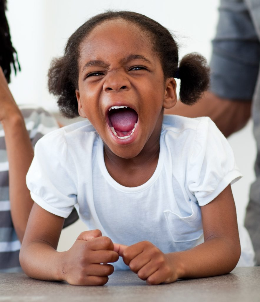 Angry little African American girl having temper tantrum.