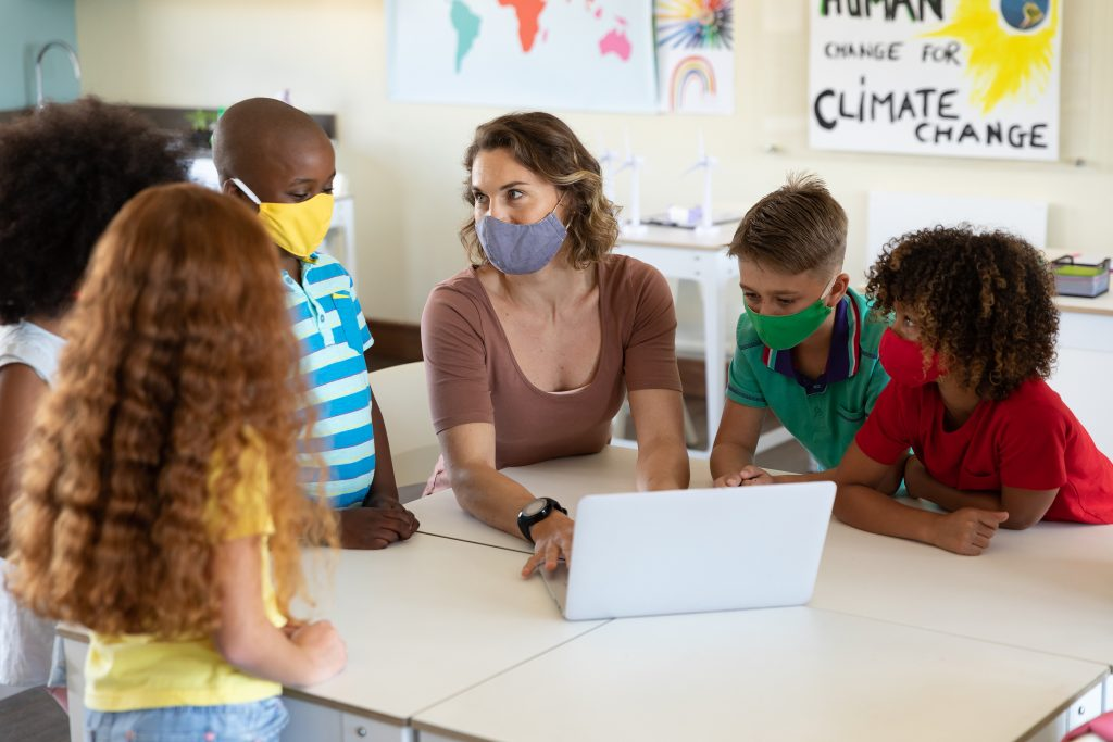 Caucasian female teacher wearing face mask at school, teaching children at school classroom.