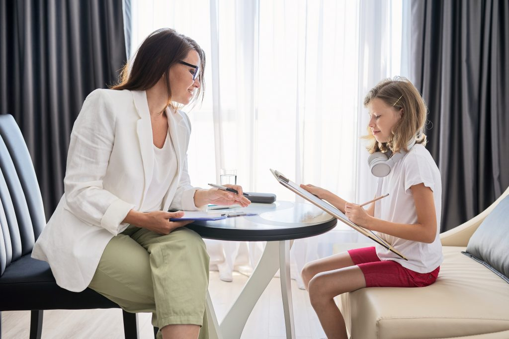 Child psychologist talking to young girl kid office. Psychology, psychotherapy, professional counseling mental help for children