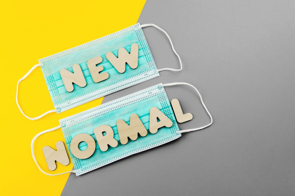 NEW NORMAL words on protective face masks on yellow and red background.