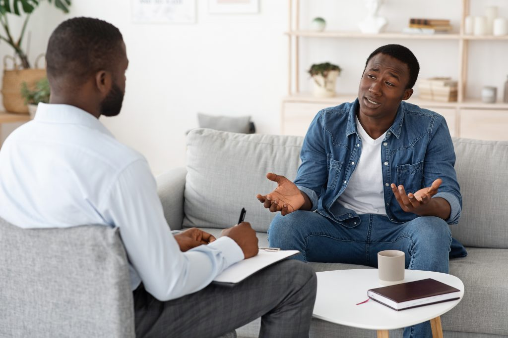 Stressed black man explaining his problems to psychologist at individual therapy session