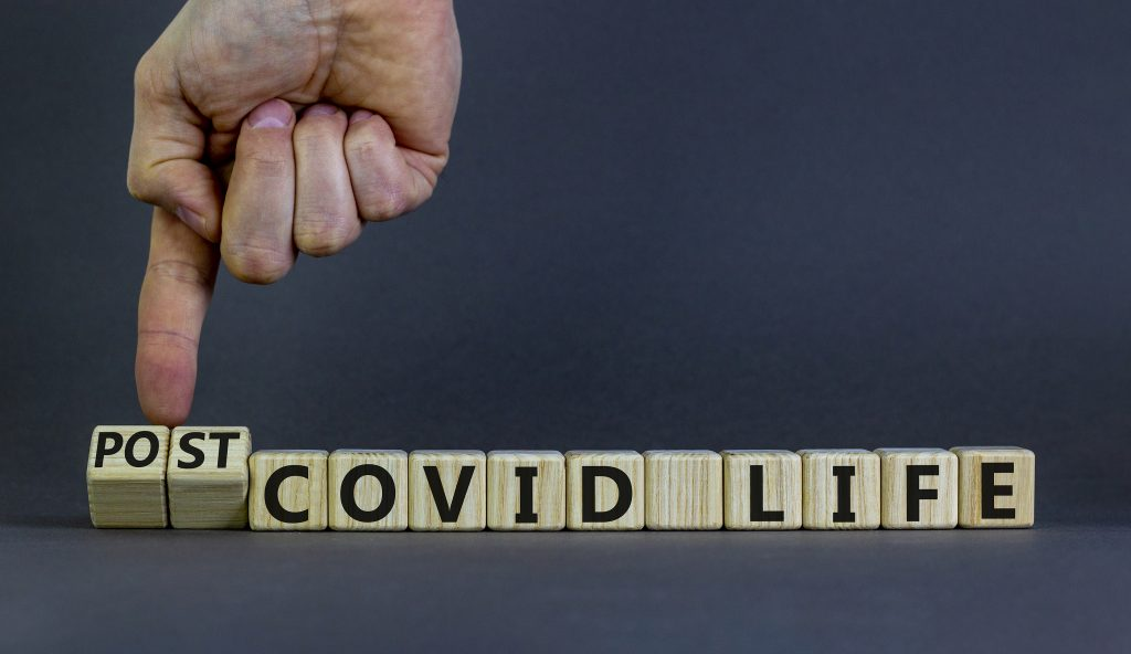 Symbol for a post-covid life. Businessman turns cubes and changes words 'covid life' to 'post-covid life'.