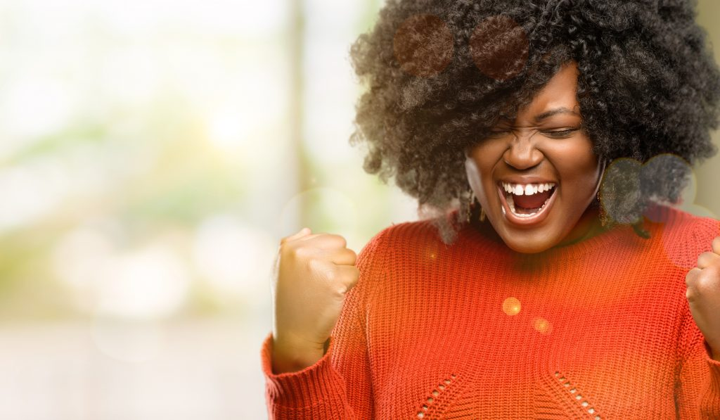 African woman happy and excited celebrating victory expressing big success, power, energy and positive emotions.