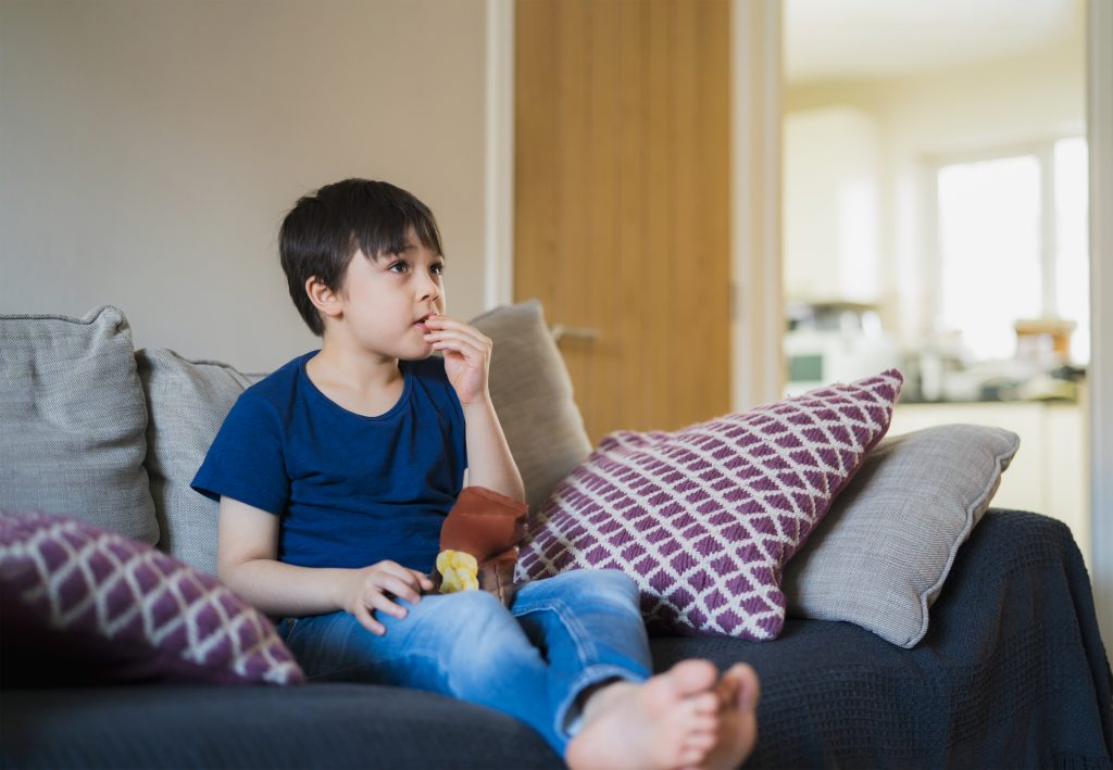 New normal lifestyle Kid sitting on sofa eating potato chips while watching TV