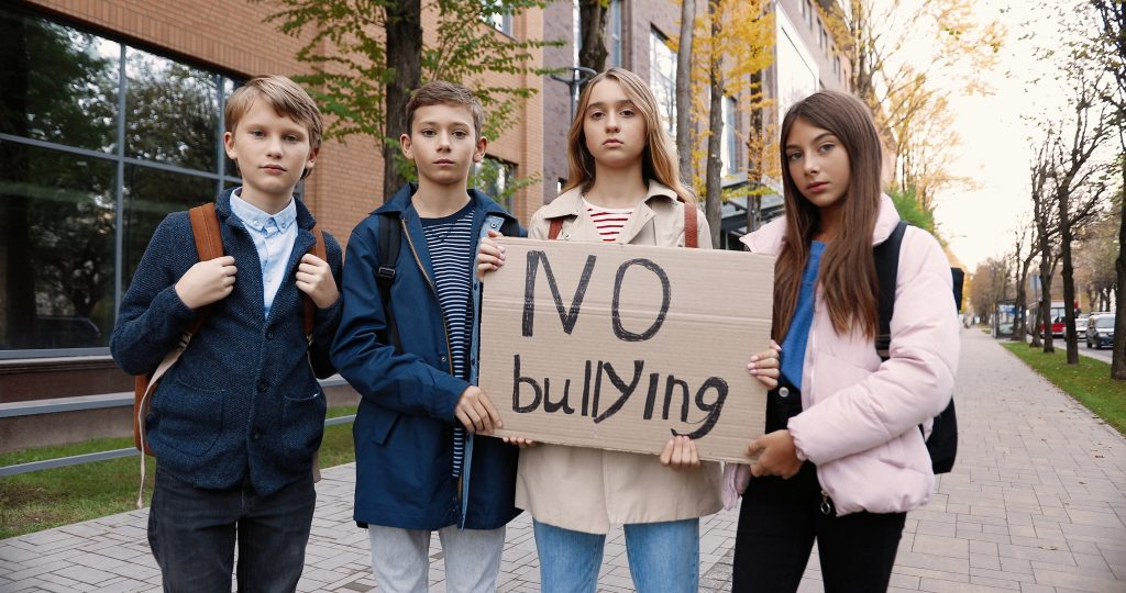 Serious teen school students standing outdoor near school and holding No bullying sign.