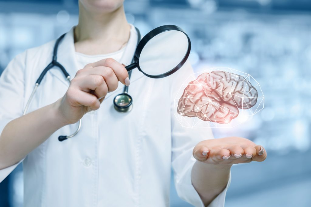 A young doctor with a magnifier is standing and looking at the brain model hanging above her hand at the blurred laboratory background. The concept of innovative approach in brain researching.