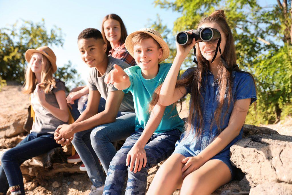 Group of children with binoculars outdoors. School outdoors.
