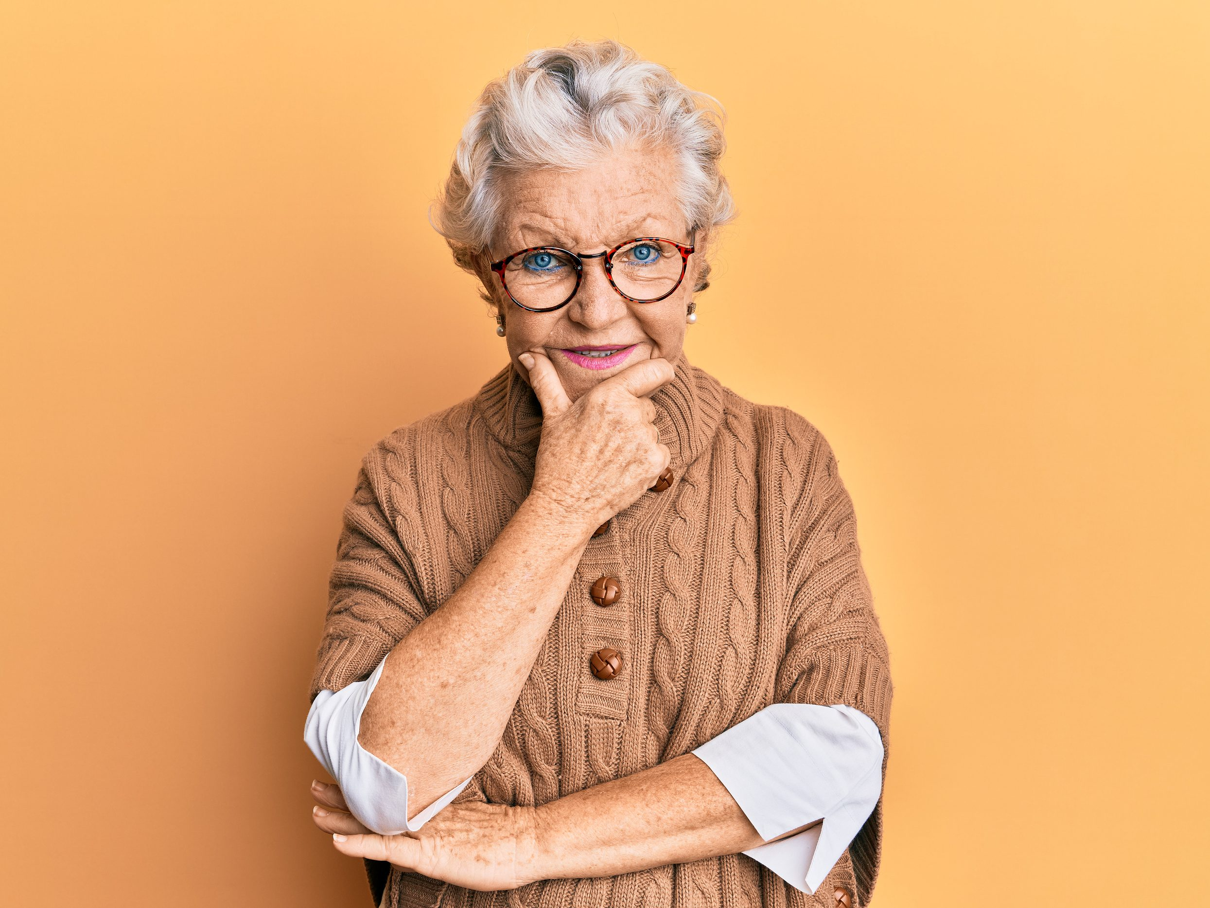 Senior grey-haired woman looking confident at the camera smiling with crossed arms and hand raised on chin. thinking positive.