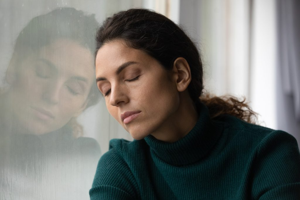 Emotionally stressed woman with head against window, eyes closed