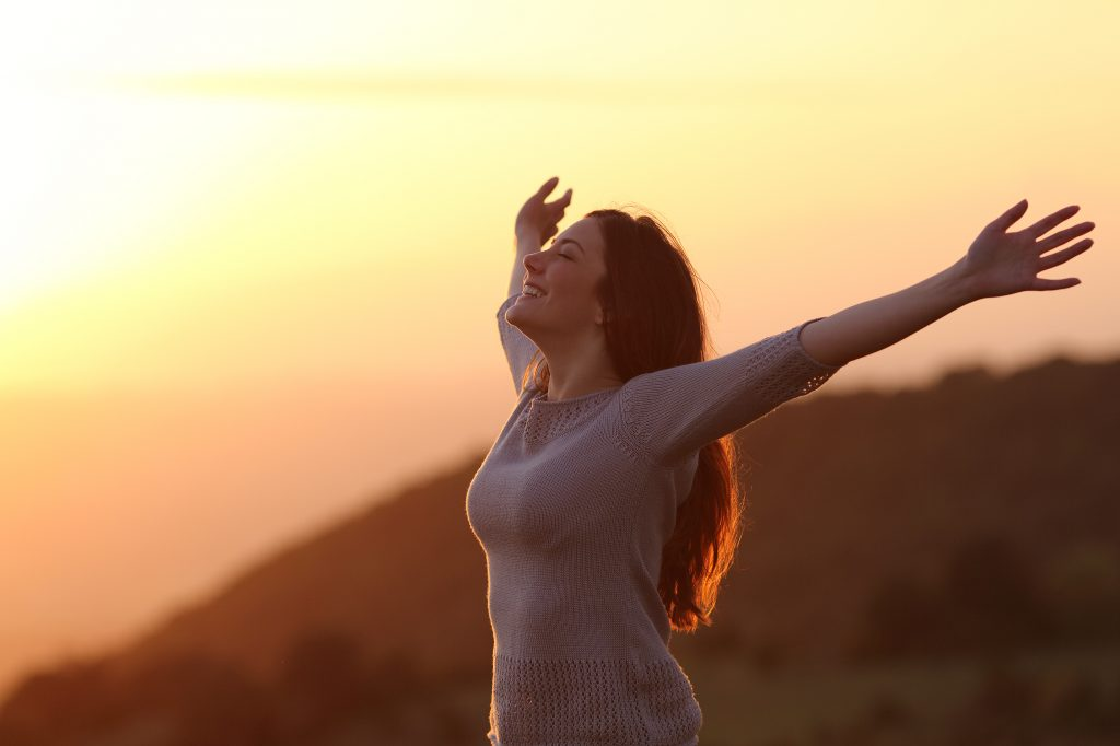 Backlit of a woman at sunset breathing fresh air raising arms, freedom