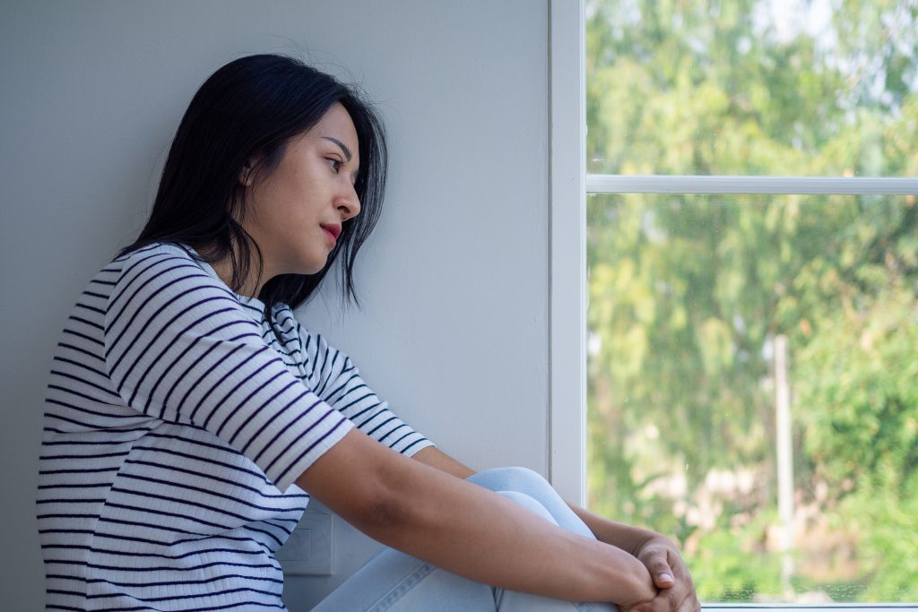 Woman beside the window, feeling sad, with guilt and shame