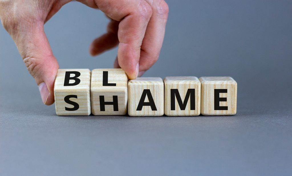 Blame or shame symbol. Hand wooden cubes and changes the word \'shame\' to \'blame\' or vice versa.